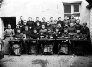 Les ouvrières de la fabrique de fleurs et Mme Bouthaud, la chef d'atelier, debout à gauche, vers 1900.